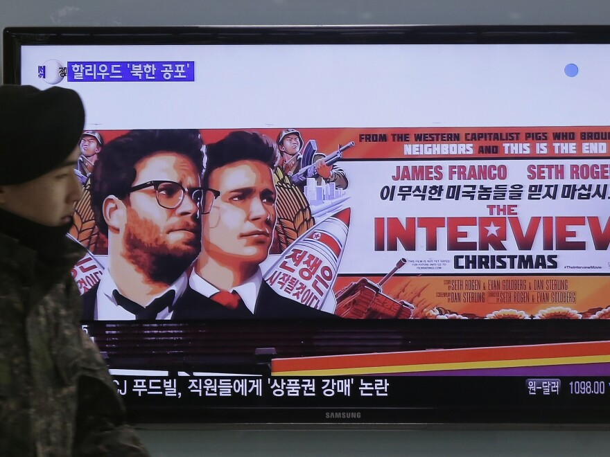 A South Korean army soldier walks near a TV screen showing an advertisement of Sony Picture's <em>The Interview</em>, which sparked condemnation in North Korea, which allegedly hacked the studio.