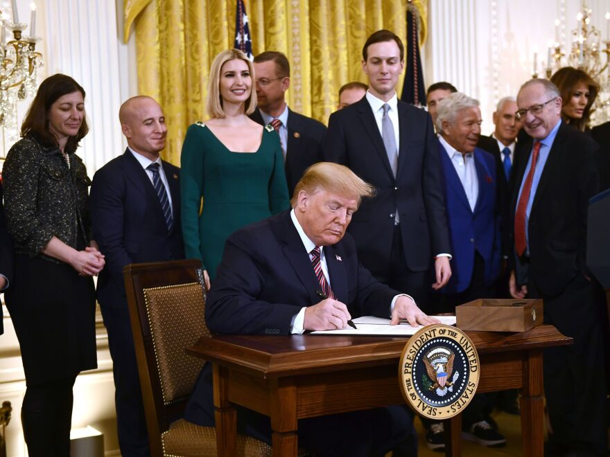 President Trump has signed an executive order that will broaden Title VI of the 1964 Civil Rights Act to apply to discrimination based on anti-Semitism. He is seen here signing the order at a Hanukkah reception at the White House.