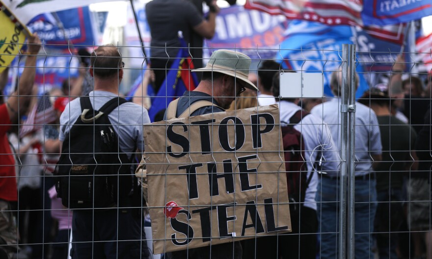 "Supporters of President Trump demonstrate at a ""Stop the Steal"" rally in front of the Maricopa County Elections Department office in Phoenix on Saturday. Domestic terrorism analysts warn that a prolonged fight and Trump's statements about the vote only fuel polarization."