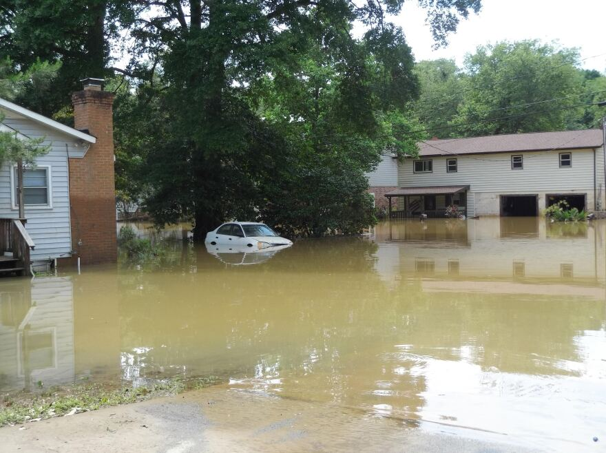 A car was still partially submerged June 10 after flooding the night before on Riverside Drive in northwest Charlotte.