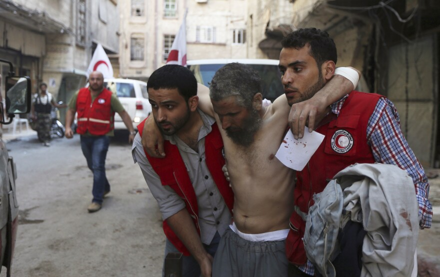 Members of the Syrian Arab Red Crescent help a man injured Tuesday in an airstrike in Damascus. Activists say the bombing was carried out by forces loyal to President Bashar Assad. After keeping his distance from Syria's civil war, President Obama said Wednesday that the U.S. military wouldn't hesitate to go after Islamic State radicals who control large parts of the country.