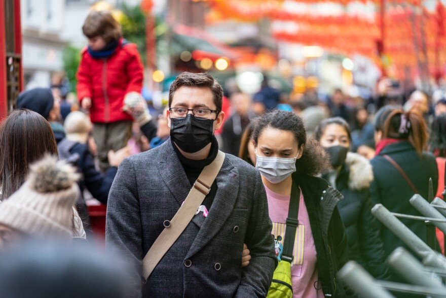 Photo of people wearing surgical masks in a crowd.