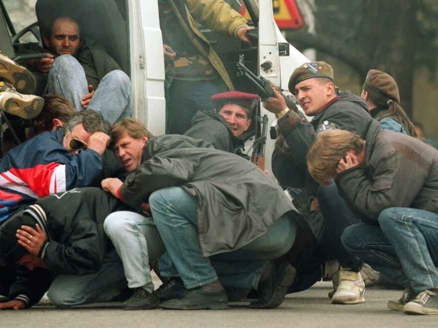 On April 6, 1992, a Bosnian special forces soldier (third from right) returns fire from Serbians opposed to Bosnian independence as civilians seek cover in downtown Sarajevo. The day marked the beginning of the 44-month siege of Sarajevo, which left 100,000 dead.