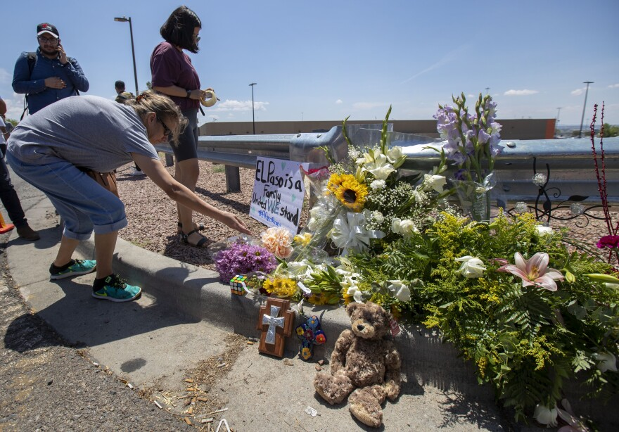 El Paso residents place flowers at a makeshift memorial for the victims of the Saturday mass shooting at a shopping complex.