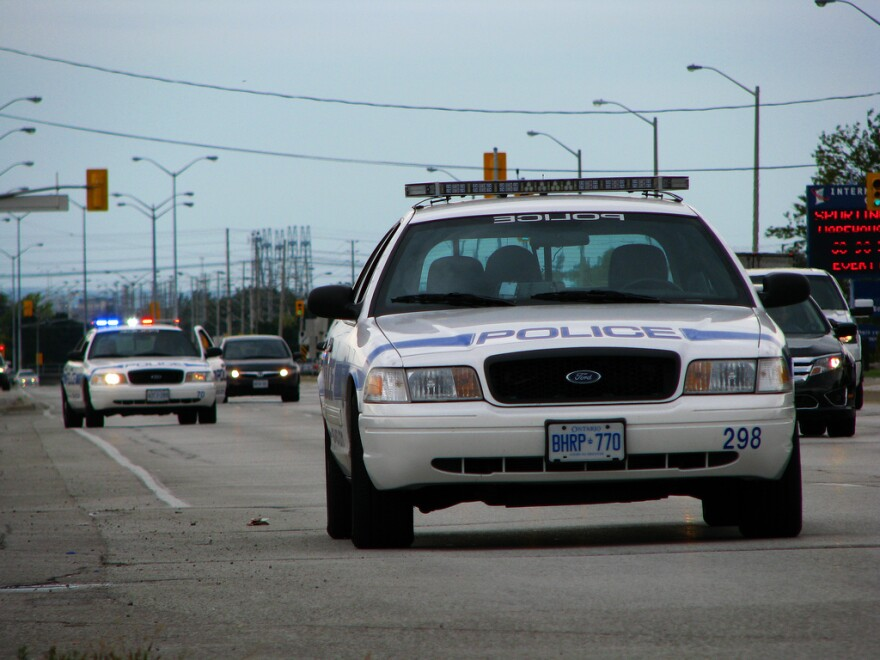 Police cars driving on the road.