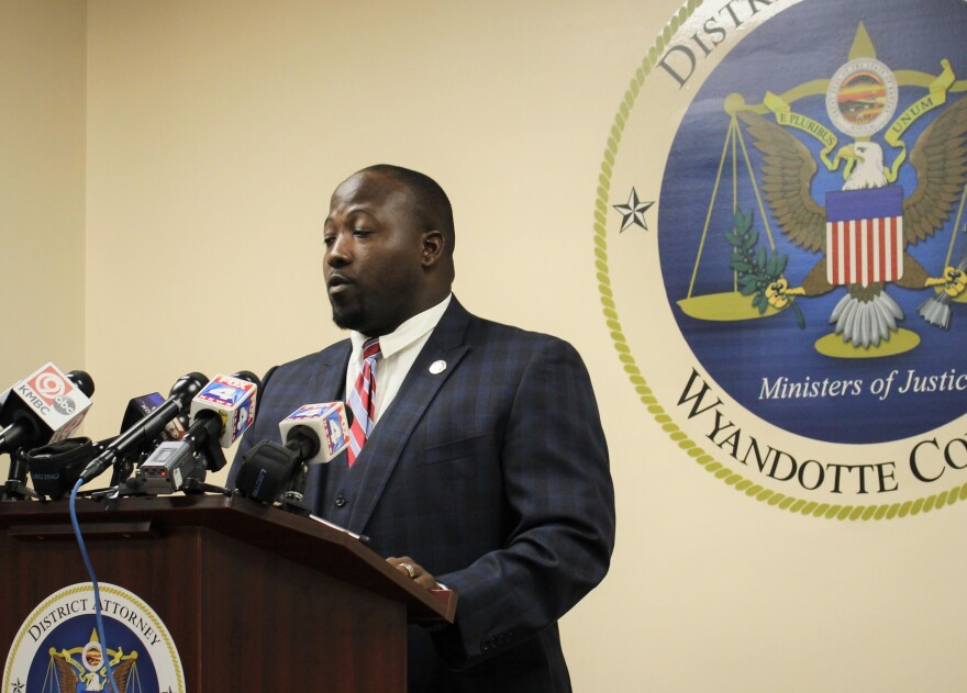 District Attorney Mark DuPree in a dark suit, white shirt and red-striped tie standing at a podium with multiple news channel microphones with the district attorneys seal on the wall behind him.