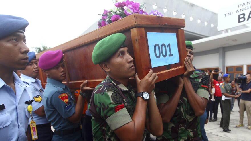 Indonesian soldiers carry a coffin containing a victim of AirAsia Flight 8501 upon arrival at Indonesian Military Air Force base in Surabaya, Indonesia, on Wednesday.