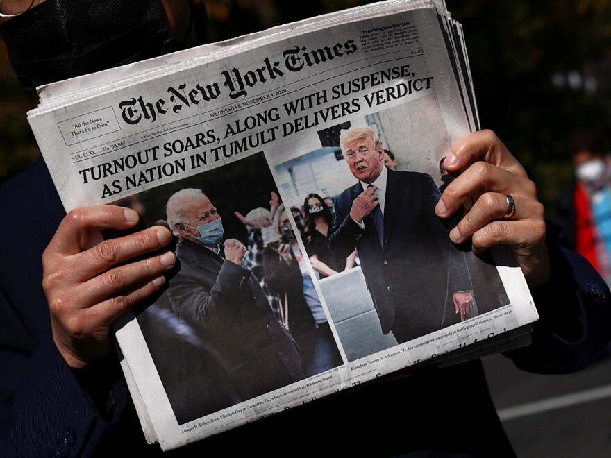 A man holds a fresh copy of <em>The New York Times</em> on Black Lives Matter Plaza near the White House on Wednesday morning.