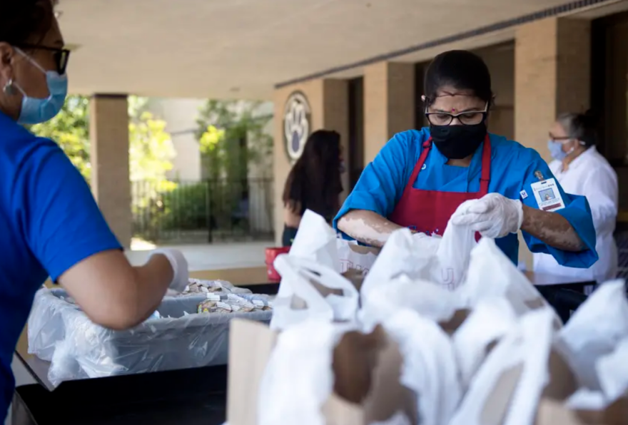 Round Rock ISD food service worker Hema Patel prepares meals to distribute to families during a curbside meal distribution at Bluebonnet Elementary School on Thursday in Round Rock.