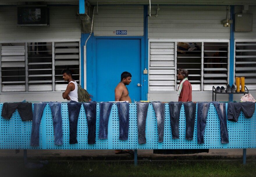 Migrant workers in Singapore congregate on the balcony of a workers dormitory now being used as an isolation facility that houses a cluster of coronavirus cases.