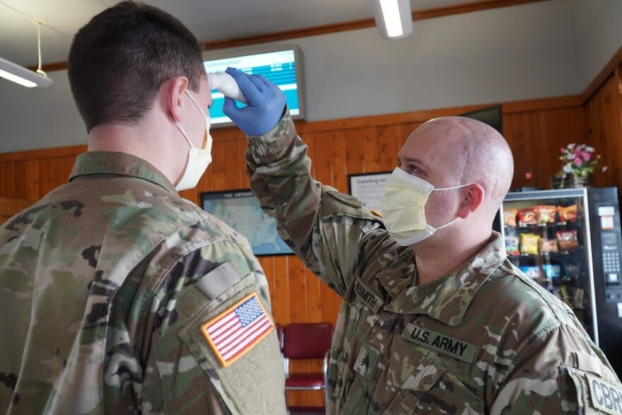 Army Sgt. Willy Nesmith from Cut Bank, Montana takes the temperature of Army Spc. Trevor Dodson as a part of daily personal wellness verification at the Amtrak Train Station in Shelby, Montana, April 3, 2020.