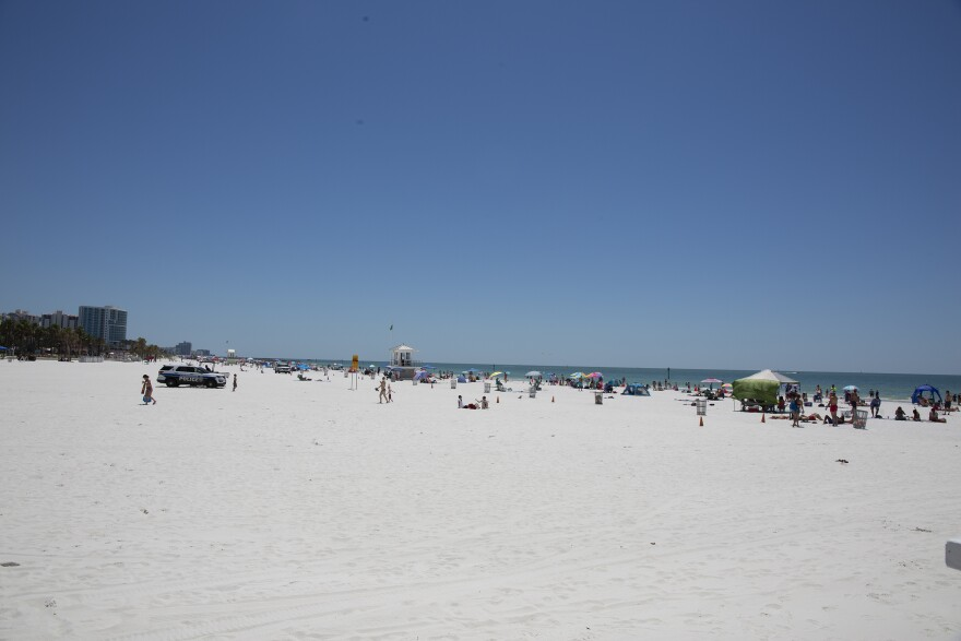 A photo of clearwater beached with people on blankets and with umbrellas all spaced out down the sand.