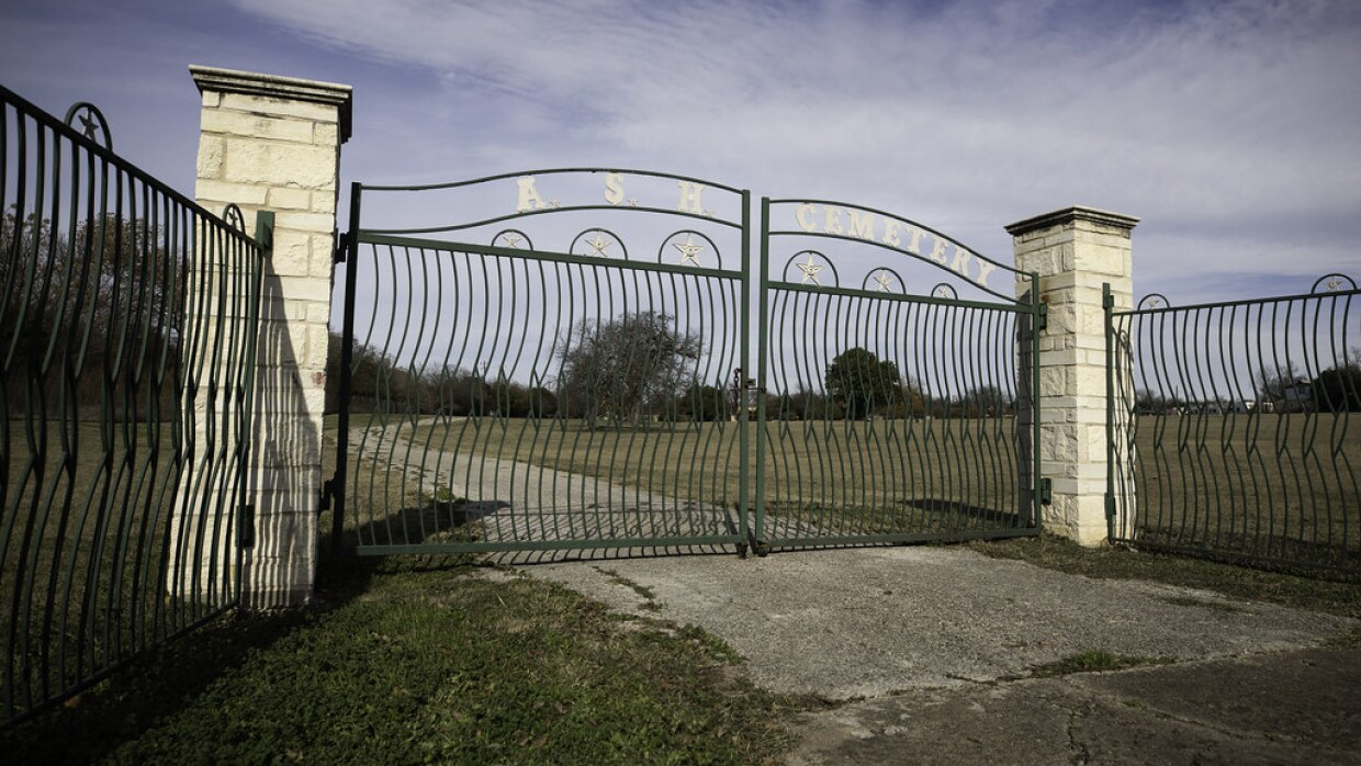 """An iron gate that says """"ASH CEMETERY"""" on it."""