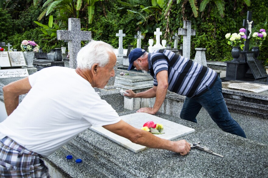 William González Rodríguez, 79, (left) cleans his wife's grave with his son, Orlando González, 54, for the first time since the hurricane. The night before, Orlando had hopped the cemetery fence and poured bleach on the grave's marble cover to loosen the grime that had built up in the 20 months since the cemetery closed.