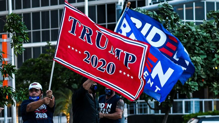 Supporters of President Trump and Democratic presidential nominee Joe Biden wave flags prior to Biden's arrival for a townhall in Miami, Florida.