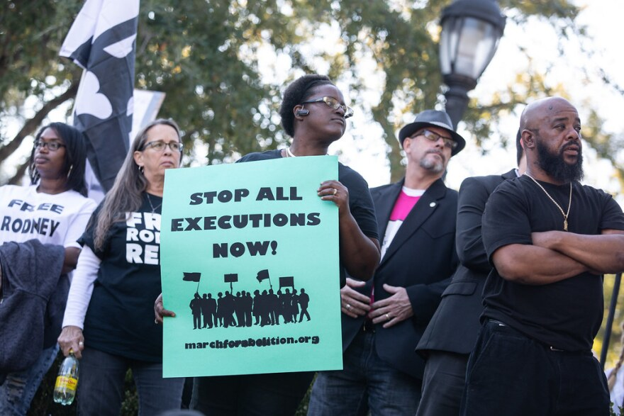 """A protester holds a sign that says """"Stop All Executions Now!"""""""