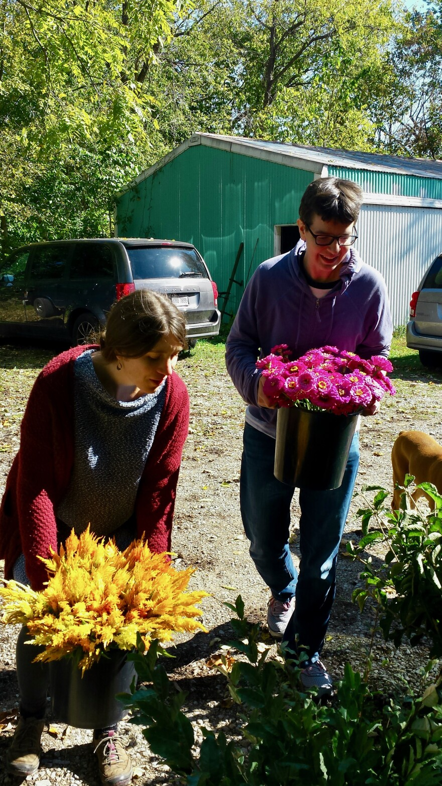 Nellie and Rosealie load flowers into the car