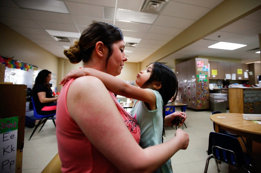 Tiffany Contreras kisses her daughter Kyndall, 4, goodbye at Disney Elementary in Tulsa, Okla. As part of a pilot program that aims to educate both children and families, Contreras takes classes at Tulsa Community College for free.