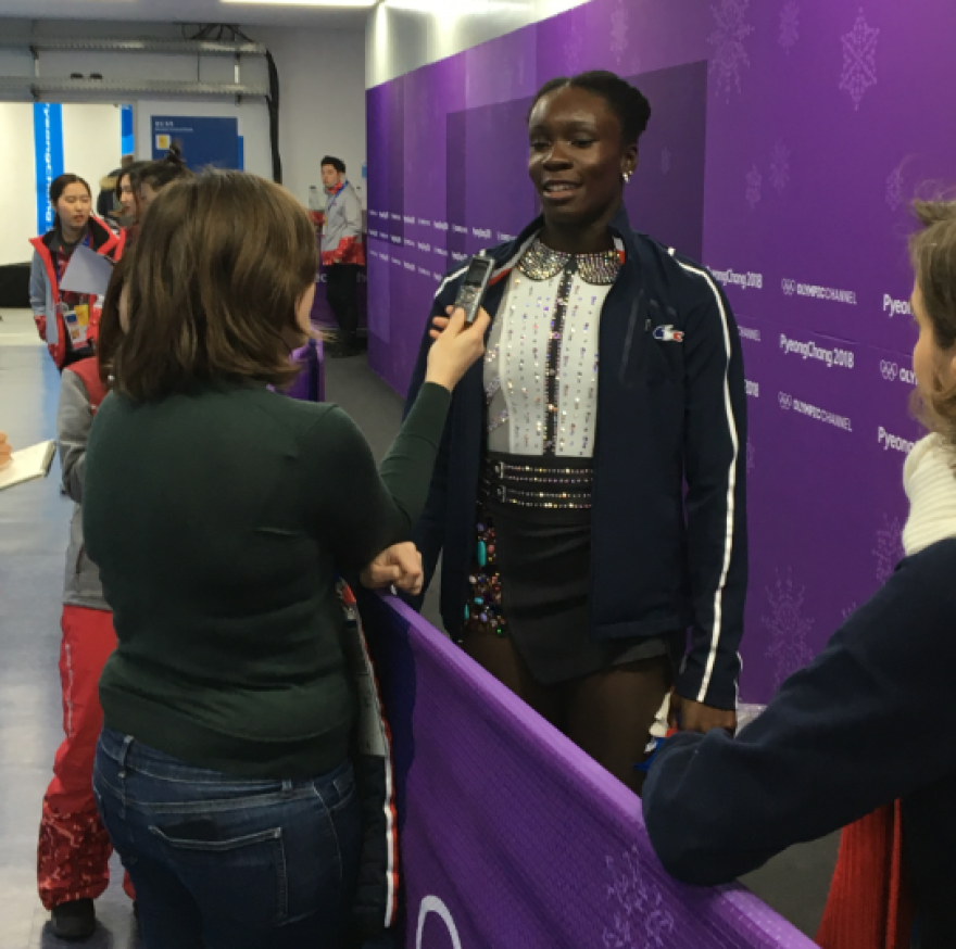"""French figure skater Mae Berenice Meite manages to catch the attention of one reporter in the mixed zone, where media members wait for athletes after they compete. Meite is a relative unknown — she finished 19th in the ladies individual event. The biggest stars are greeted by a throng of journalists. """"I'm taking my time to make my own history,"""" Meite said."""
