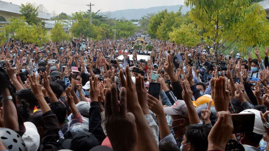 Mourners raise three fingers to the sky as the body of Mya Thwet Thwet Khine is taken to be buried. The gesture of solidarity, introduced in <em>The Hunger Games</em>, has been adopted by Myanmar activists.
