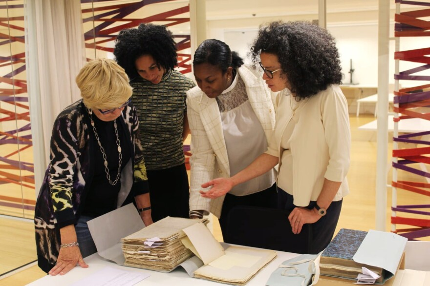 Valika Smeulders (far right), head of history at Amsterdam's Rijksmuseum, explains what is included in a stack of colonial documents at the National Archives in The Hague to (right to left) Peggy Bouva, Jessica Bouva and Maartje Duin's mother Albertin Duin-van Lynden.