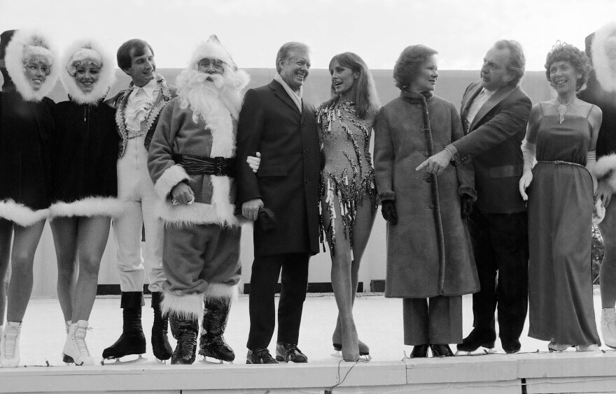 President Jimmy Carter joins Santa and ice skating star Peggy Fleming at a White House reception in 1980, where she and other skaters provided the entertainment.