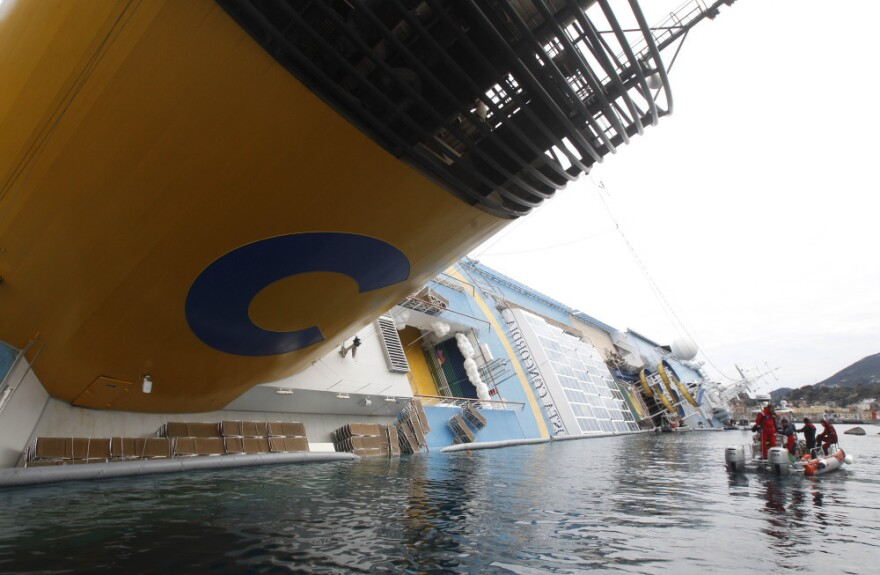 Italian firefighters scuba divers approach the grounded cruise ship Costa Concordia off the Tuscan island of Giglio, Italy on Friday.