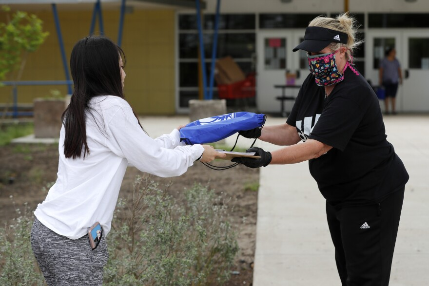 Educator with mask on gives chrome book to student in front of school building.