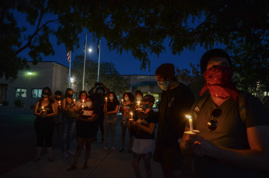 Nighttime photo of a crowd wearing masks and holding candles.