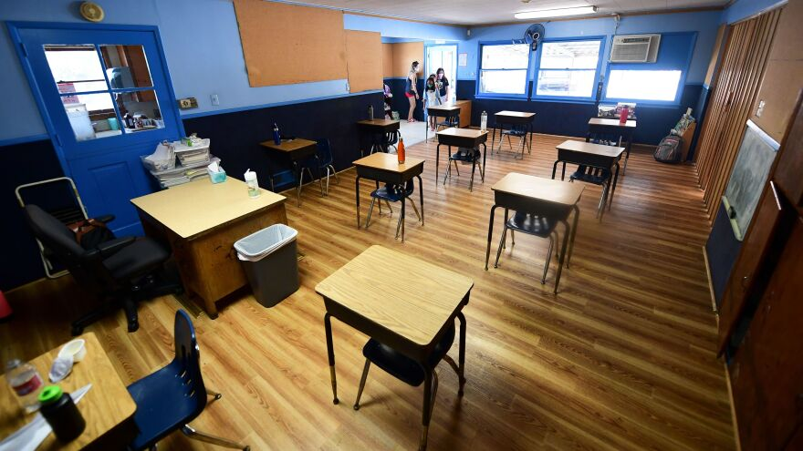 Children in an elementary school class wearing masks enter the classroom with desks spaced apart as per coronavirus guidelines in Monterey Park, Calif.