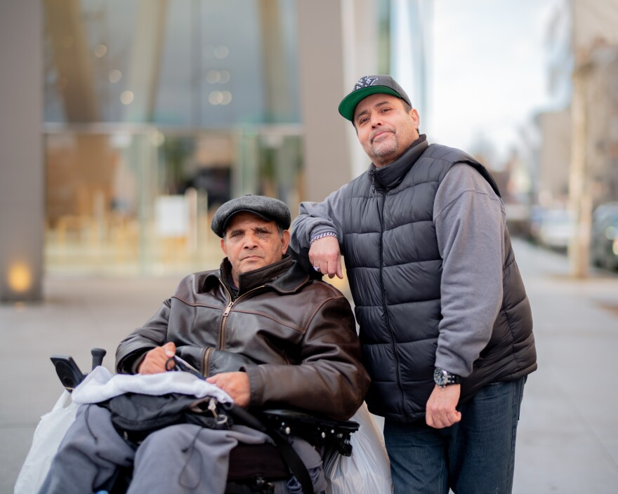 """Angel Padilla (right) works as Boudhas Mohammed's home attendant and says he's always aware of spreading germs. """"I don't want nothing to rub off on him, so I wear a mask and gloves,"""" Padilla says. """"In my job, it's a universal precaution. So this coronavirus ain't scaring me, because I protect myself."""""""