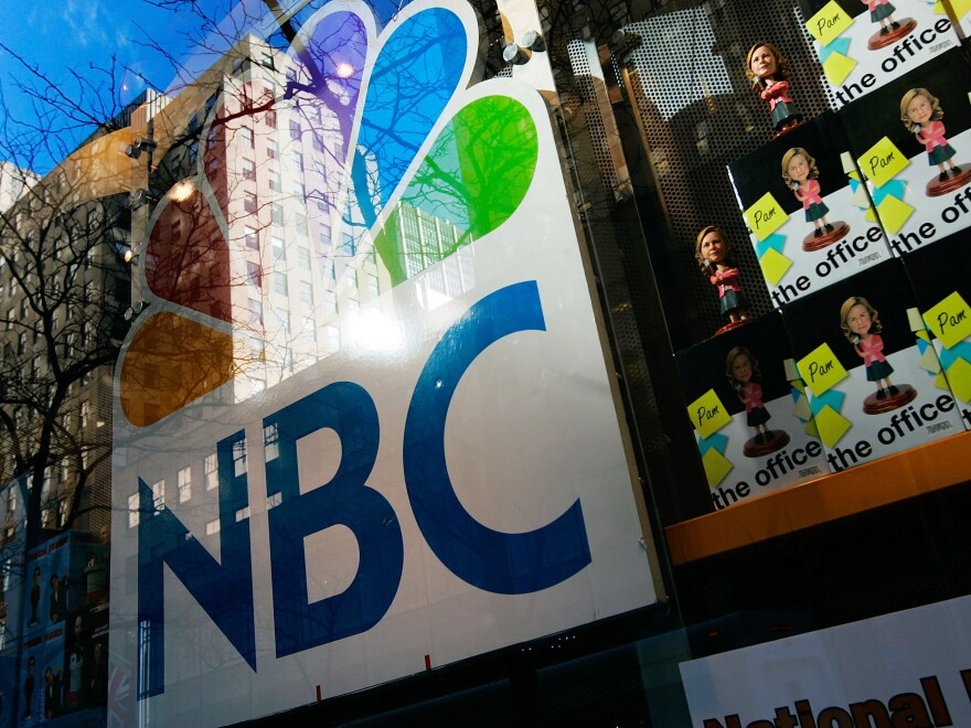 An NBC store is seen through a window reflecting Rockefeller Center in New York City. Comcast, the nation's largest cable company, has owned 51 percent of NBCUniversal since 2011.