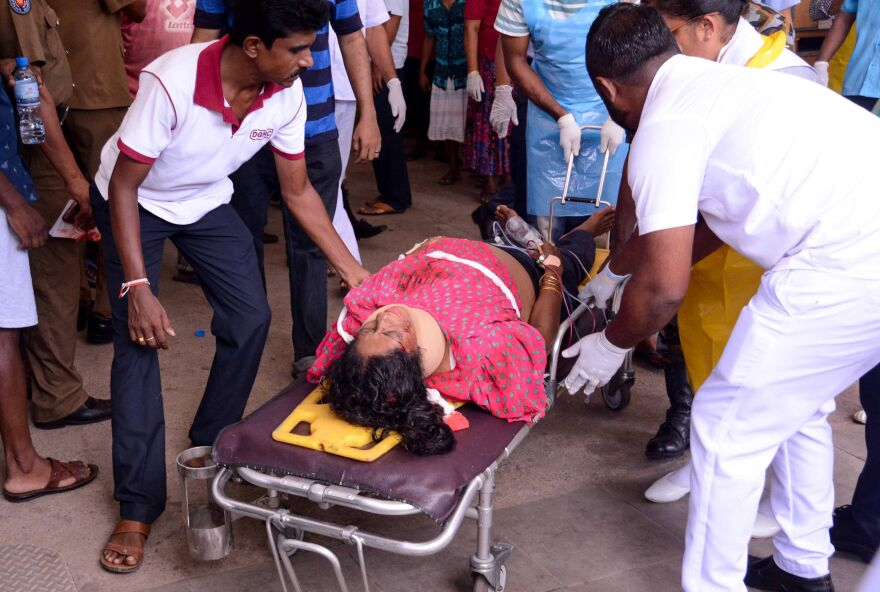 An injured Sri Lankan woman lies on a stretcher as hospital workers transport her at the District General Hospital in Negombo, following the explosion at St. Sebastian's Church.