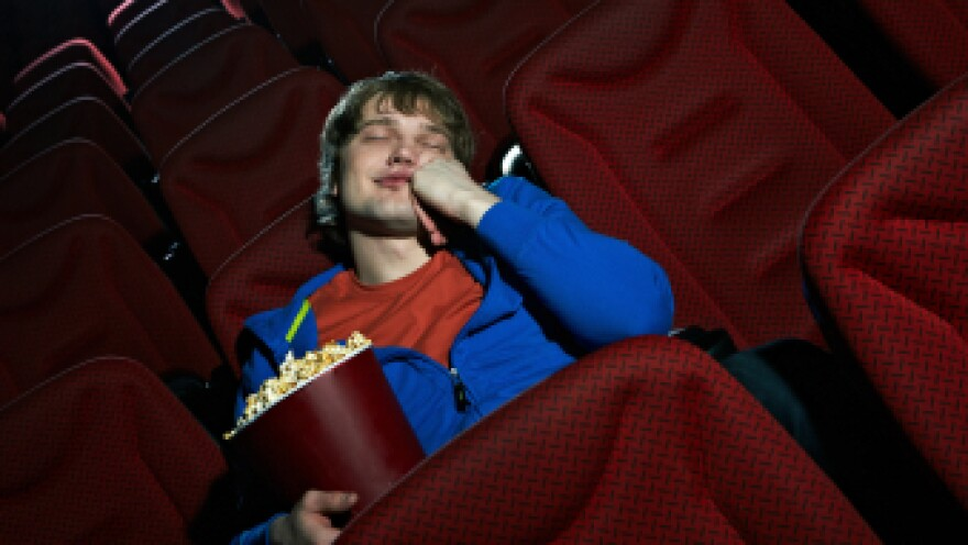 A man sleeps in a movie theater.