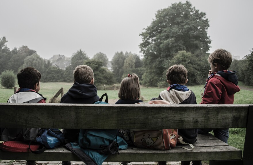 Children sitting on a bench look out at a park