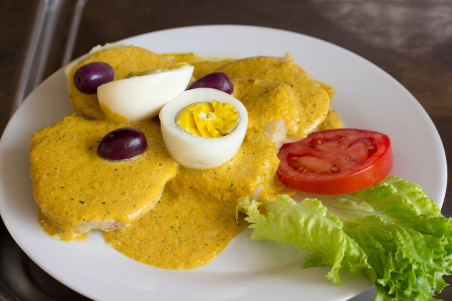 <em>Ocopa</em> is a traditional Andes dish made with slices of potato topped with a nutty, creamy sauce, hard-boiled eggs and olives.