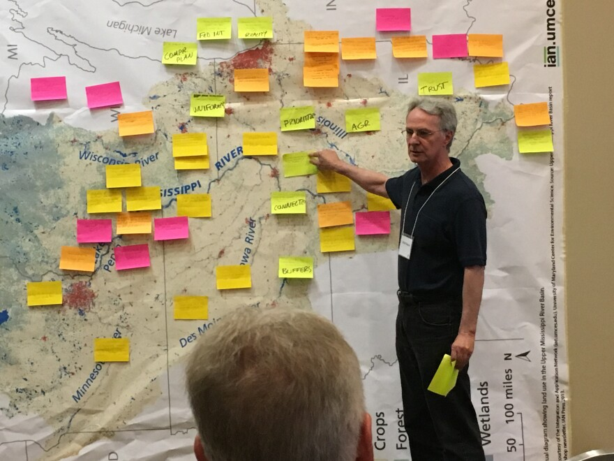 Brad Walker, rivers director at the Missouri Coalition for the Environment, stands in front of a map of the upper Mississippi River region where attendees of a river summit have posted their concerns about handling sediment and flooding.