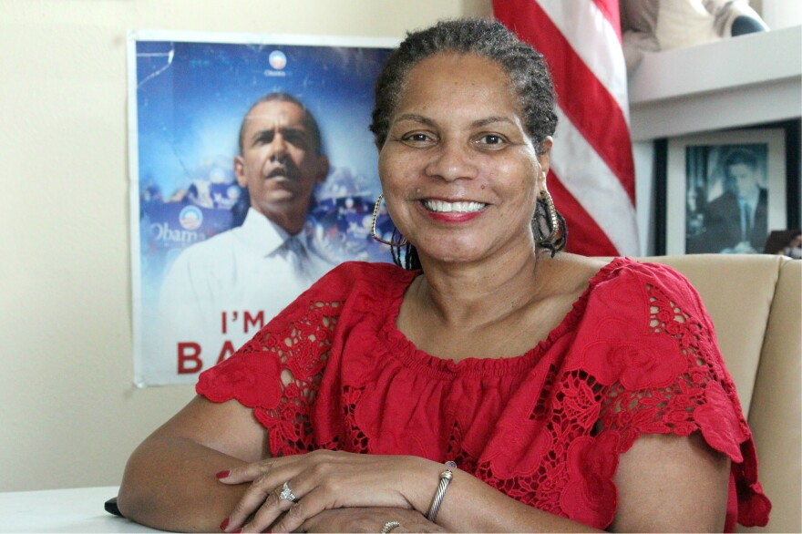 Deborah Peoples sitting at a desk with an American flag and a poster of Barack Obama in the background.