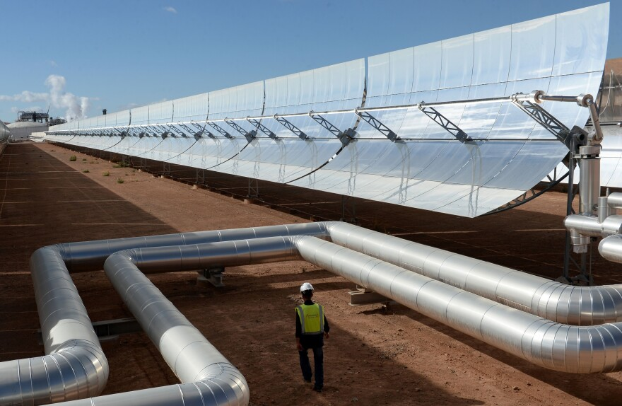 A worker walks past solar mirrors at the Noor I plant in October, while engineers were preparing for the plant's official launch.
