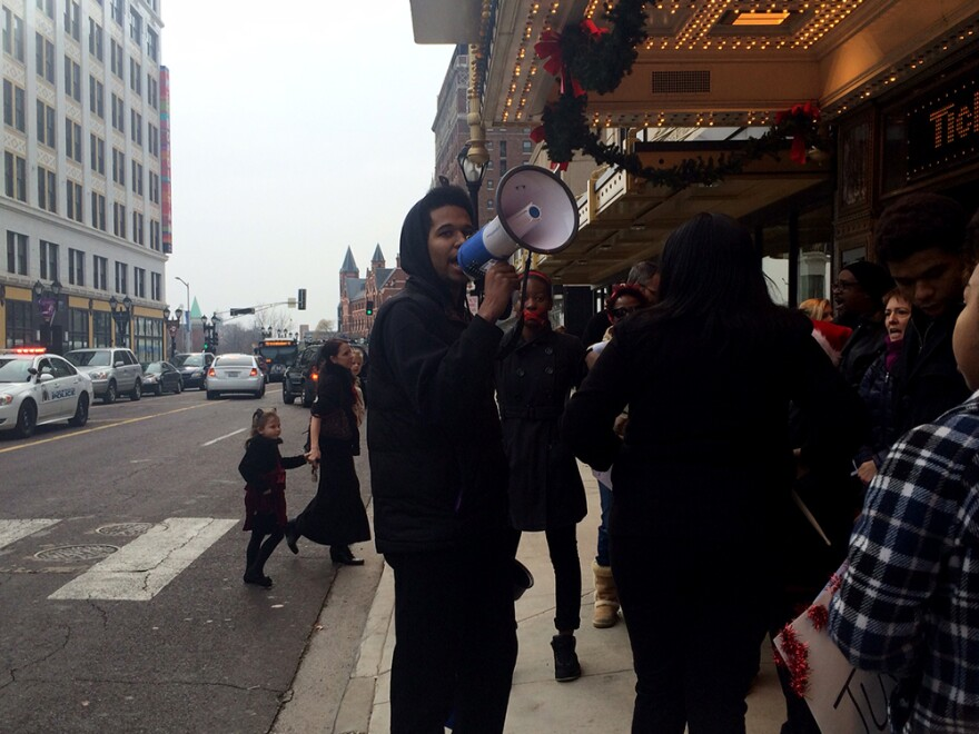 Jonathon Pulphus leads protesters in song as theater goers cross the sidewalk to see Annie on Sunday, Dec. 7, 2014.
