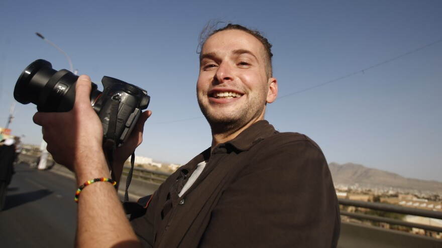 In this 2013 photo, Luke Somers, 33, an American photojournalist who was kidnapped over a year ago by al-Qaida, poses for a picture during a parade marking the second anniversary of the revolution in Sanaa, Yemen.