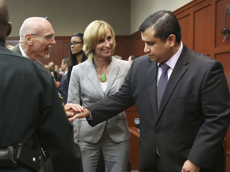 George Zimmerman (right) is congratulated by his defense team Saturday night after being found not guilty of murder in the shooting death of Trayvon Martin.
