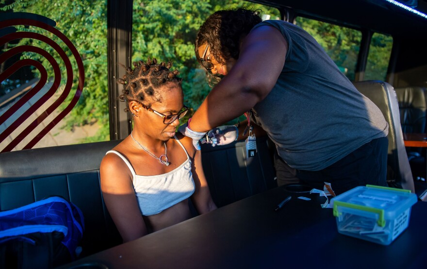 Dotson gives a flu shot to Sopain Lawson, who lives in a homeless encampment under a bridge in downtown Atlanta. It can take several encounters to gain someone's trust and get them to accept medical care, the health team finds.