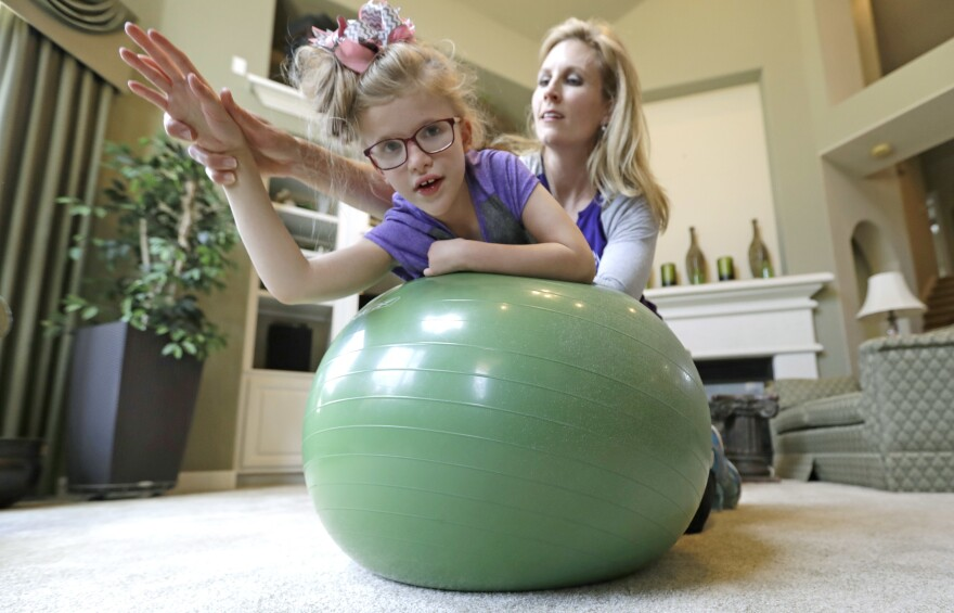In this 2017 photo, Stacey English works on balance and core strength with her 7-year-old daughter, Addison, in Houston. Parents are stepping in even more during the pandemic since therapists can't work with students with disabilities in person.