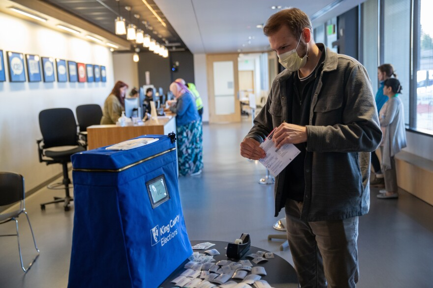 Taylor Miller prepares to cast his ballot during early voting on Monday in Renton, Wash. King County has had the highest number of deaths in the U.S. linked to the coronavirus outbreak.