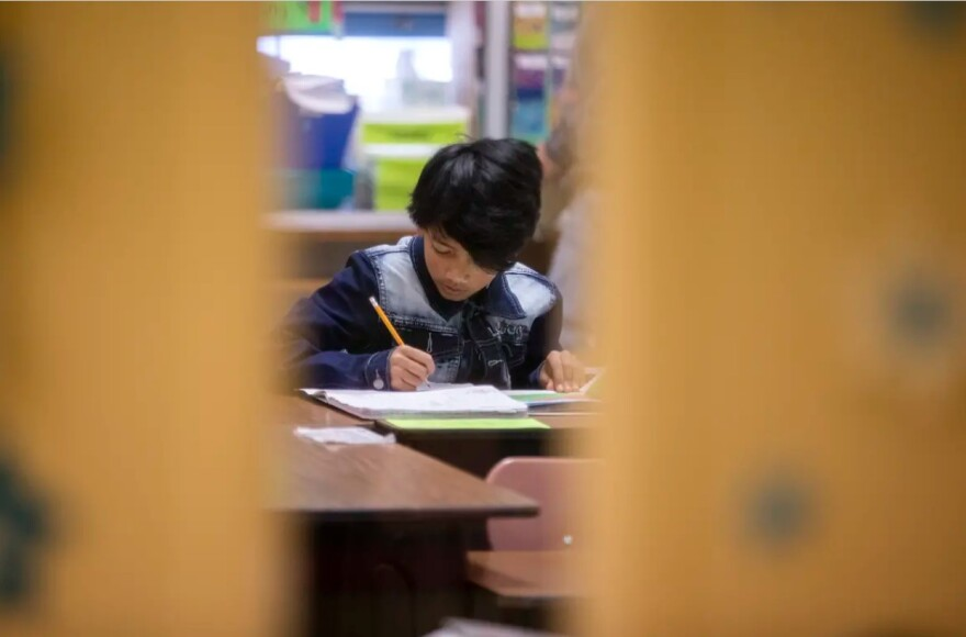 A child sits at a desk writing on paper.