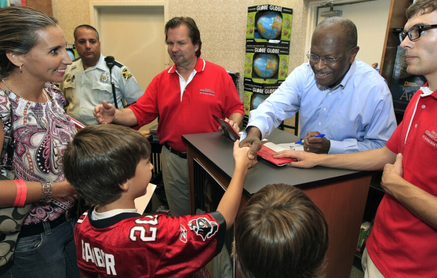 <p>Herman Cain shakes hands with a family at a Petersburg, Fla. book signing, Wednesday, Oct. 5, 2011.</p>
