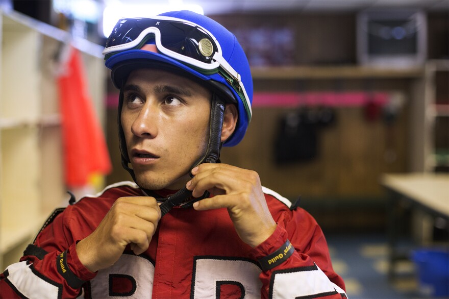 Javier Tavares watches the track on a locker room TV set while getting ready for the first race of opening day.