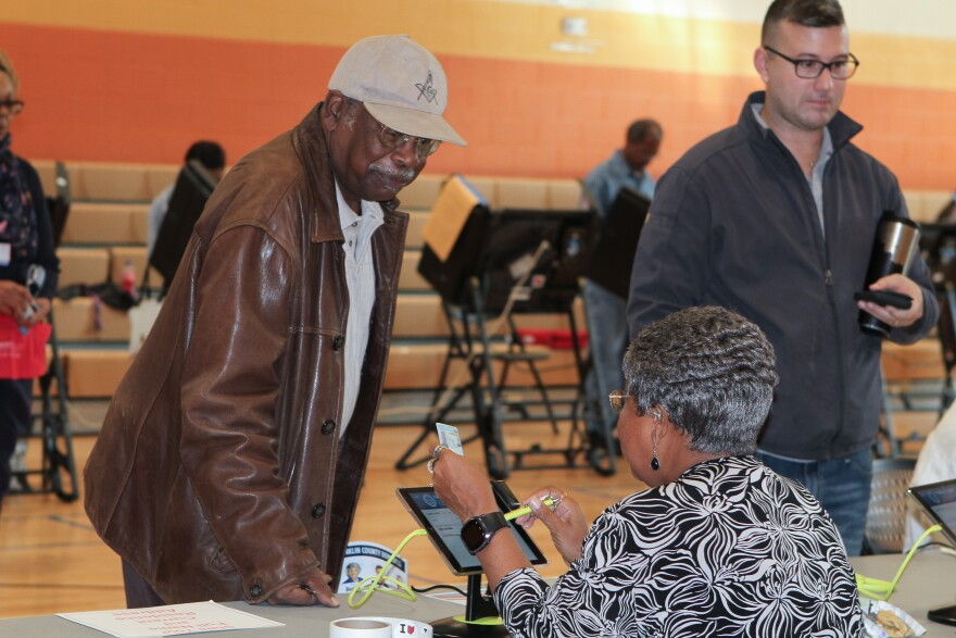 man checking in with woman to vote