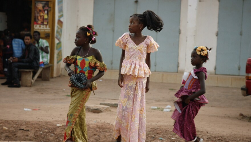 Three girls are on a street in Banjul, Gambia's capital.